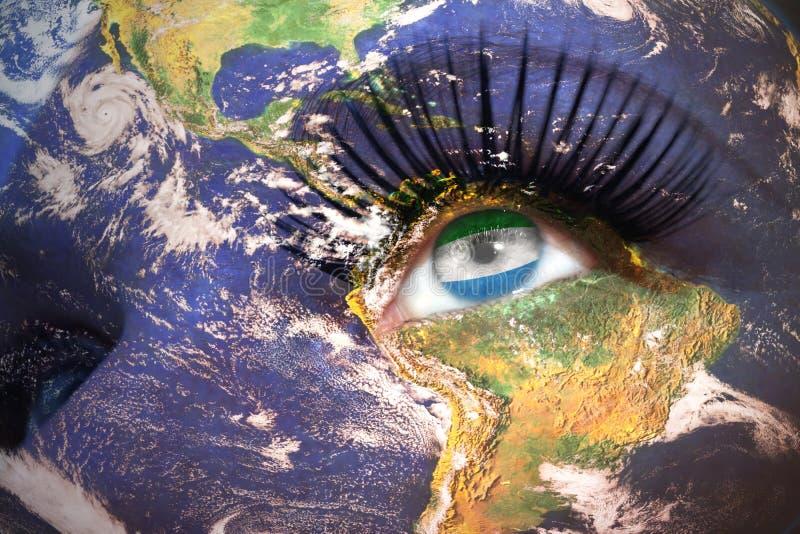 La cara de la mujer con textura de la tierra del planeta y bandera de Sierra Leona dentro del ojo imagenes de archivo