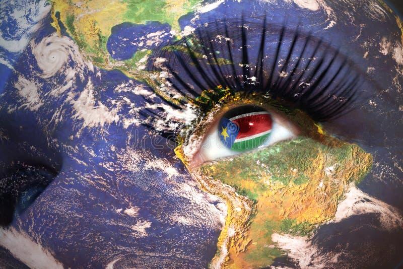La cara de la mujer con textura de la tierra del planeta y bandera del sur de Sudán dentro del ojo fotos de archivo libres de regalías