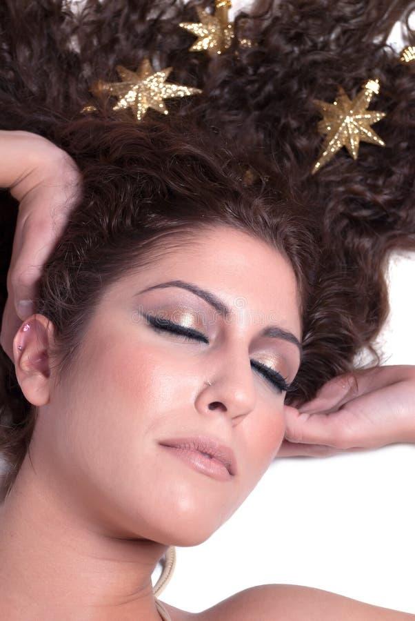 La cara de la mujer femenina atractiva con oro protagoniza en su pelo foto de archivo