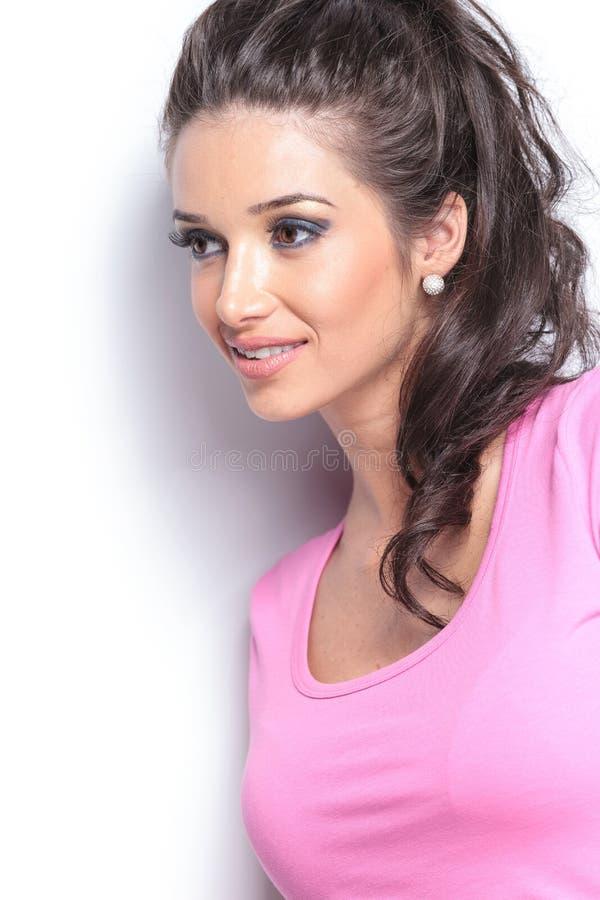 La cara de la mujer sonriente joven que mira lejos imagen de archivo libre de regalías