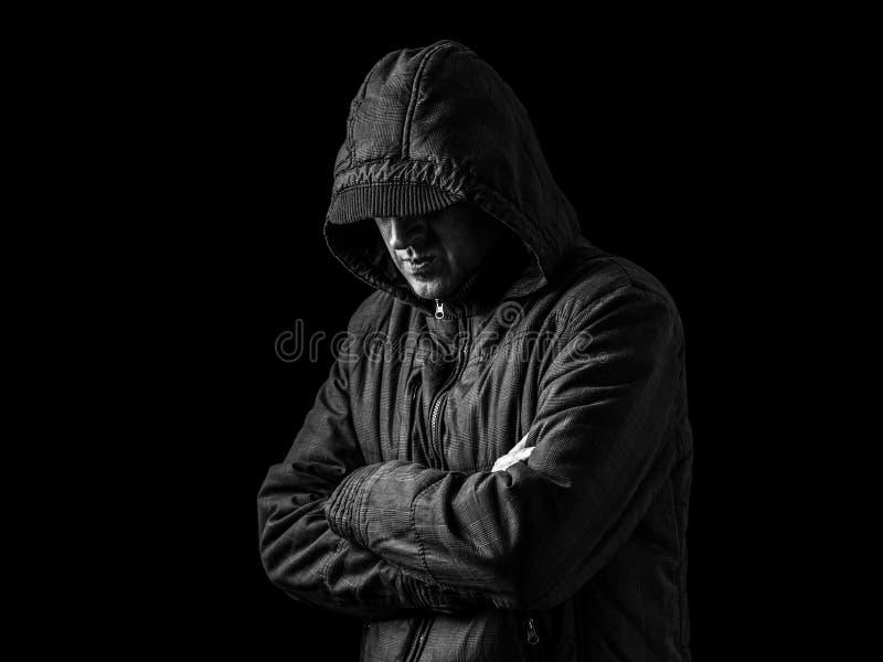 La cara de ocultación del hombre sola, deprimida y frágil, arma cruzado y colocándose en la oscuridad imágenes de archivo libres de regalías
