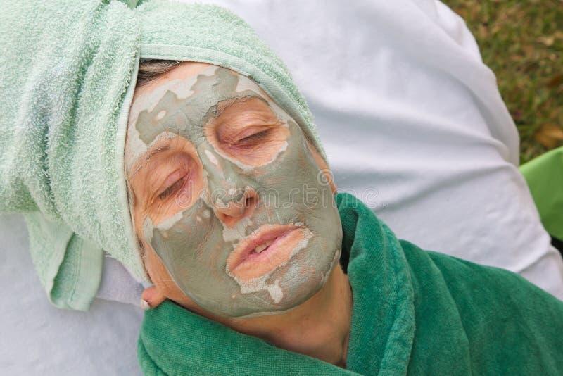 La cara de un mayor es cubierta por la máscara facial de la arcilla Cierre para arriba imagenes de archivo