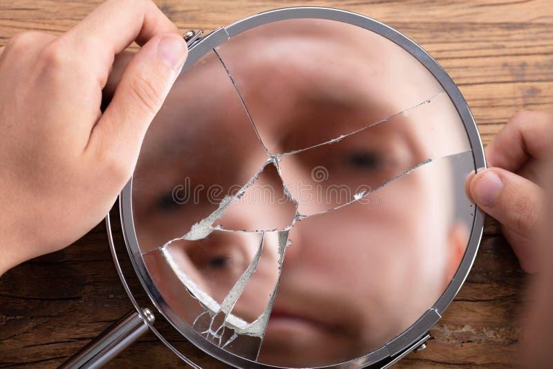 La cara del hombre en espejo quebrado fotos de archivo