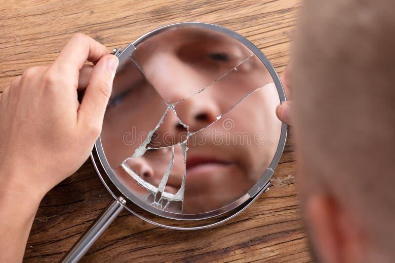 La cara del hombre en espejo quebrado imagen de archivo