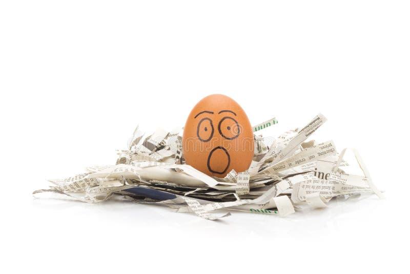 la cara del huevo chocada en los periódicos recicla imagenes de archivo