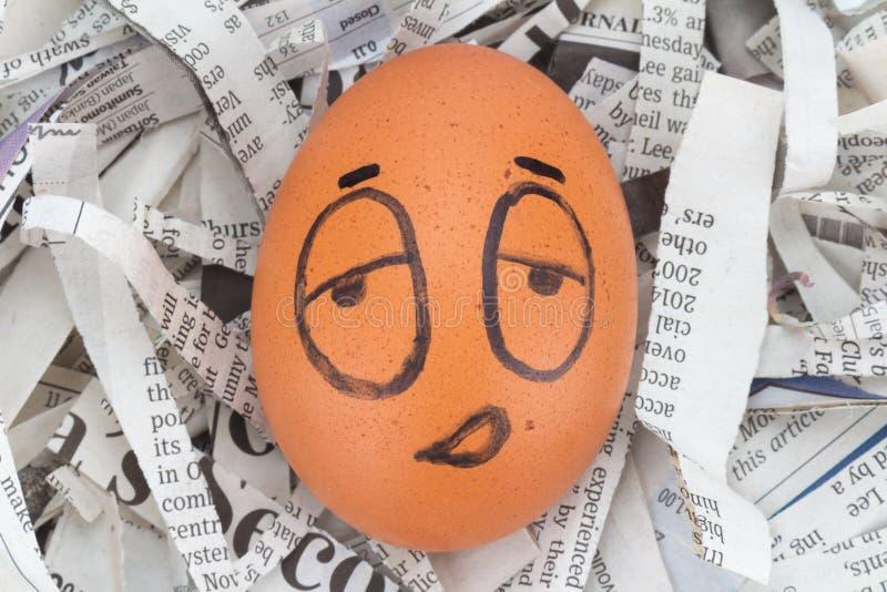 la cara del huevo soñolienta en los periódicos recicla fotografía de archivo