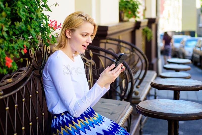 La cara entusiasta de la mujer con smartphone crea la cita en red social y espera la terraza del café de los amigos Espera de la  fotos de archivo libres de regalías