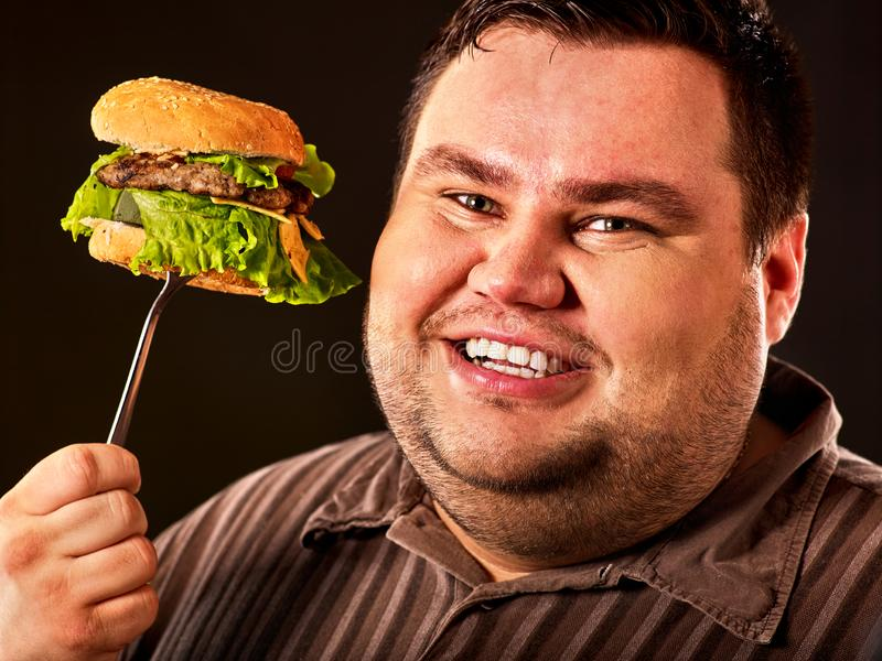 La cara gorda del hombre come la hamburguesa en la bifurcación imagen de archivo