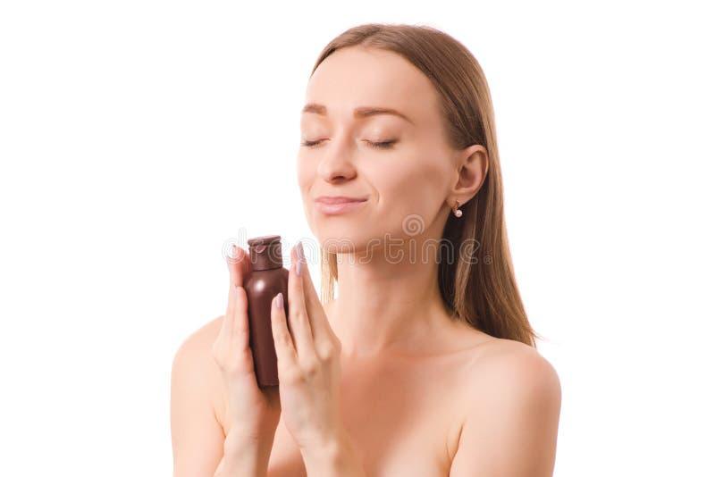 La cara hermosa de la botella de la belleza de la mujer joven con los cosméticos para el cuerpo y la cara engrasan la loción foto de archivo