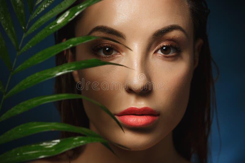 La cara hermosa de la mujer con la moda compone en fondo azul fotos de archivo libres de regalías