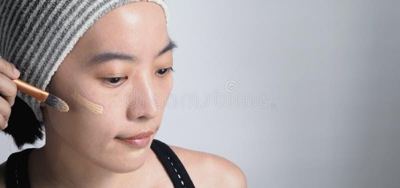 La cara hermosa de la mujer asiática compone por el líquido de la fundación fotografía de archivo libre de regalías