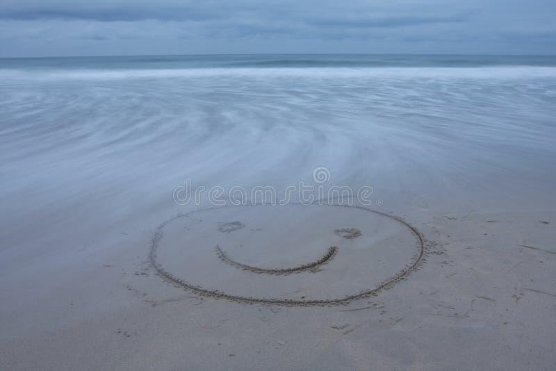 La cara sonriente drenó en la playa foto de archivo