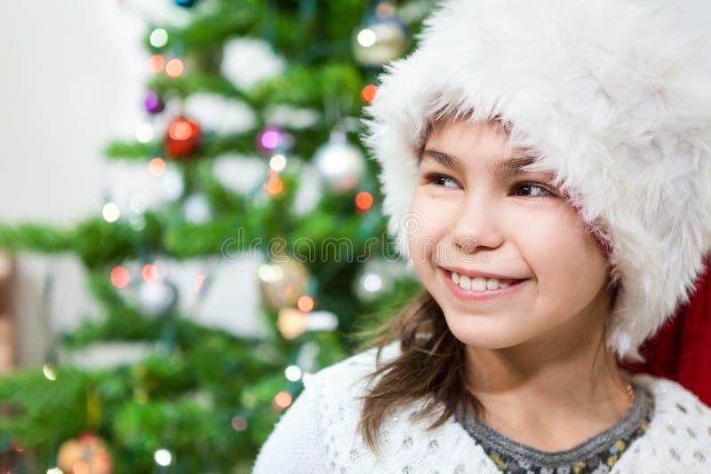La cara sonriente en muchacha bonita joven en el sombrero blanco de Papá Noel, copia el espacio imagenes de archivo