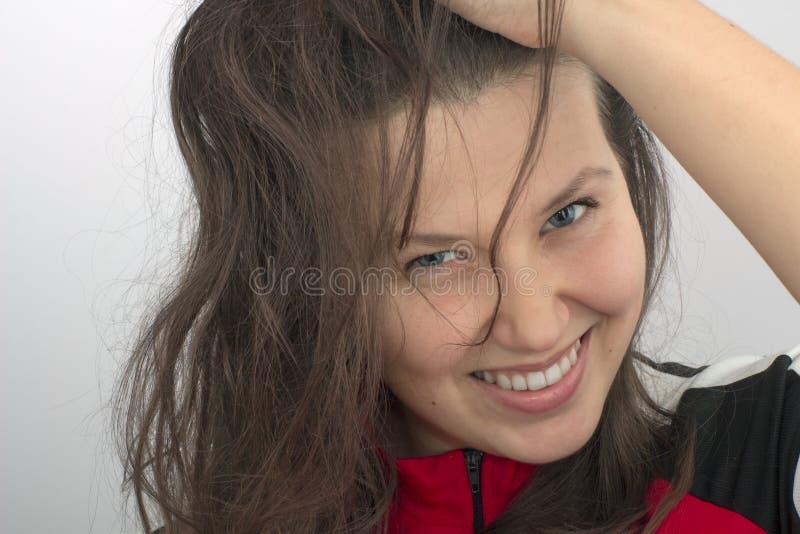 La cara y la mano de la muchacha sonriente que despeinan el pelo fotografía de archivo libre de regalías