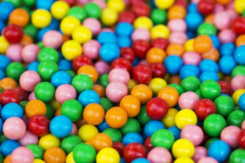 La caramella variopinta dell'arcobaleno ha ricoperto i pezzi del cioccolato in un fuoco selettivo della ciotola immagine stock