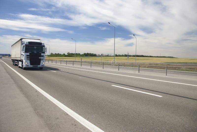 La caravane de cargaison se précipite le long de la route photo libre de droits