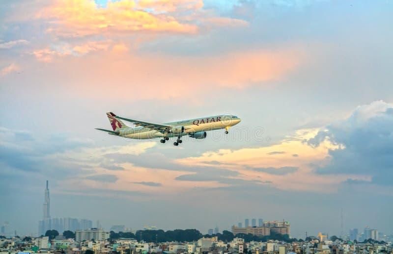 La cargaison d'Airbus A330-200F Qatar Airways à voler au-dessus des nuages préparent Tan Son Nhat International Airport de débarq photo stock