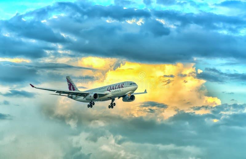 La cargaison d'Airbus A330-200F Qatar Airways à voler au-dessus des nuages préparent Tan Son Nhat International Airport de débarq images stock