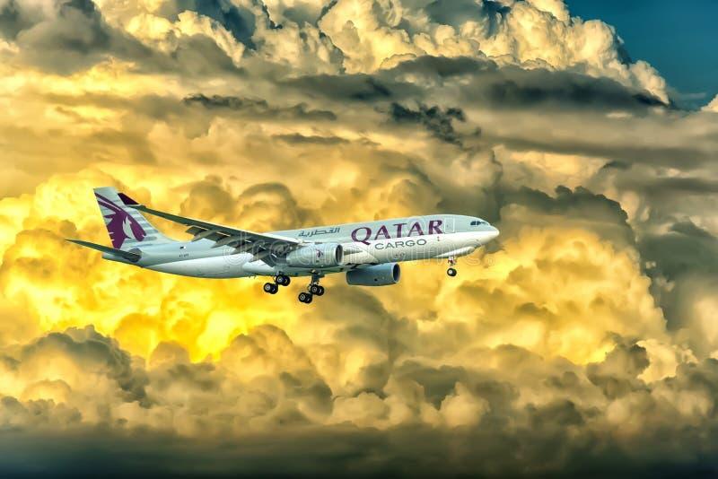 La cargaison d'Airbus A330-200F Qatar Airways à voler au-dessus des nuages préparent Tan Son Nhat International Airport de débarq photographie stock libre de droits