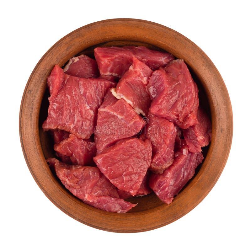 La carne cruda è pezzi incisi in un piatto marrone Isolato su bianco fotografie stock libere da diritti