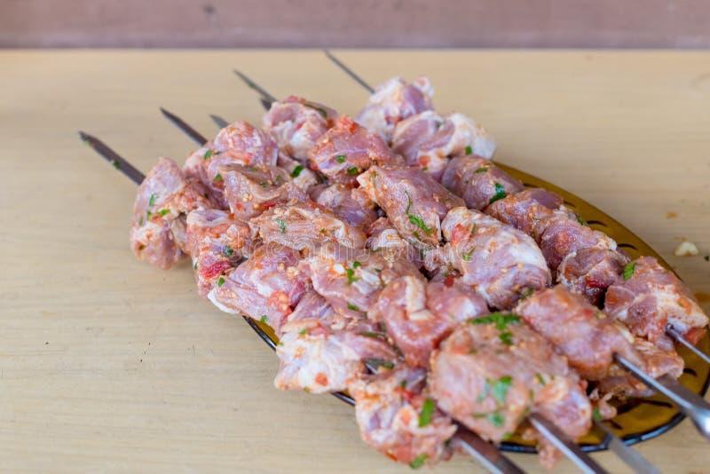 La carne cruda fresca ensarta kebabs en la placa Carne preparada para adobar en tabla de cortar Kebab, carne cruda y verduras enc imagenes de archivo