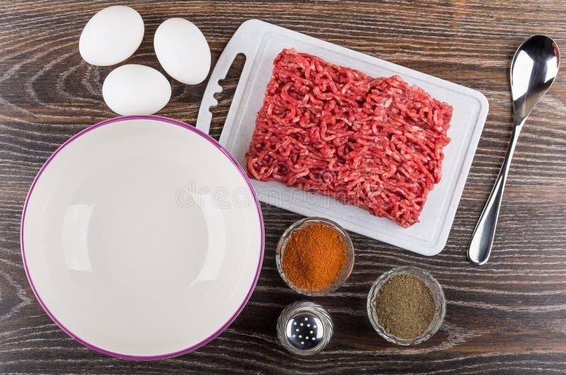 La carne de vaca pica, roja y negra pimienta, huevos del pollo, sal, cuchara fotos de archivo