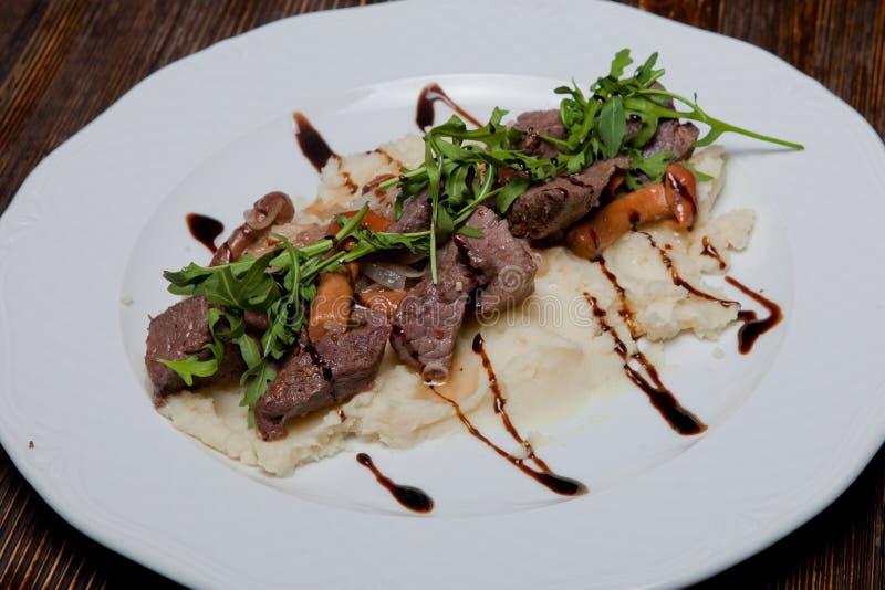La carne del verro fritta con le cipolle e il harnirovane pidpenkamy hanno schiacciato il po fotografia stock