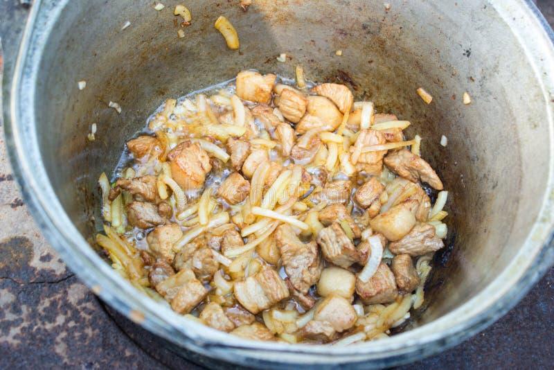 La carne e le cipolle sono arrostite in un calderone fotografia stock