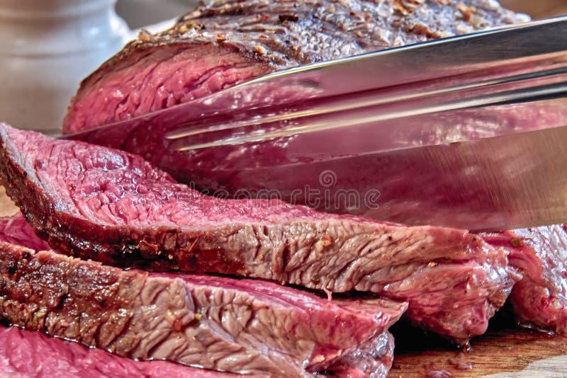 La carne frita con sangre se corta con el cuchillo de caza Primer hecho pozo del filete Estilo rústico imagen de archivo