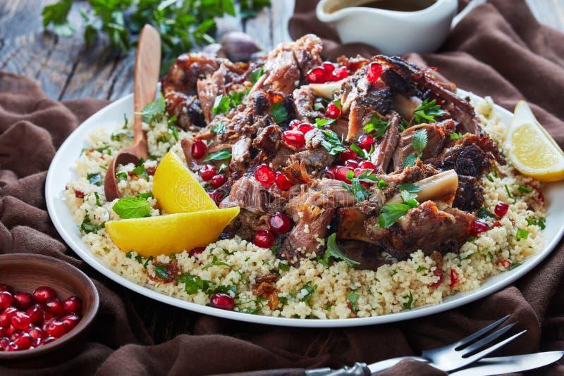 La carne lenta dell'arrosto di agnello va in pezzi servito con l'insalata del prezzemolo del cuscus, spruzzata con i semi del mel immagini stock libere da diritti