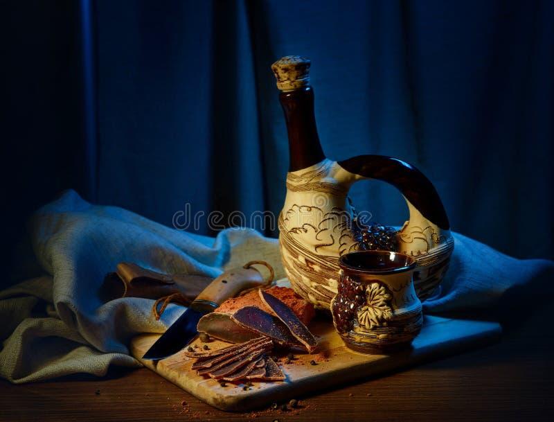 La carne secada, basturma miente en un tablero de madera con las alcaparras y las especias Cerca está un jarro de la arcilla y un imágenes de archivo libres de regalías