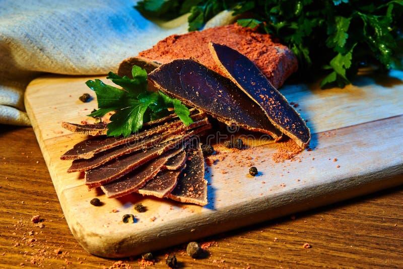 La carne secada, basturma miente en un tablero de madera con las alcaparras y las especias Perejil fresco fotografía de archivo libre de regalías