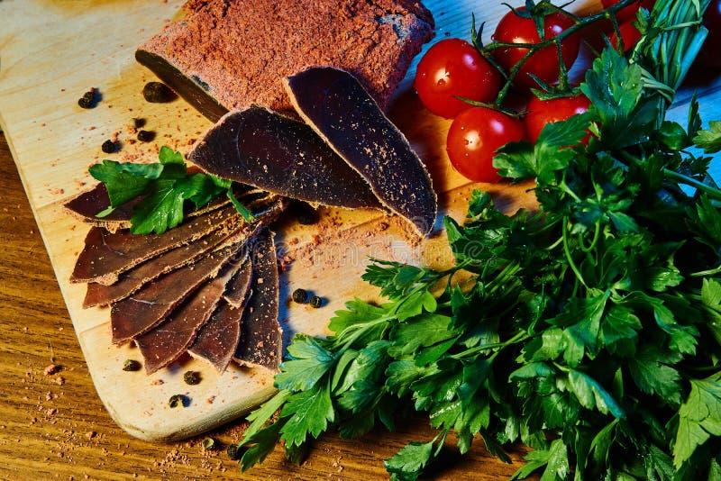 La carne secca, basturma si trova su un bordo di legno con i capperi e le spezie prezzemolo fresco e pomodori ciliegia rossi fotografia stock