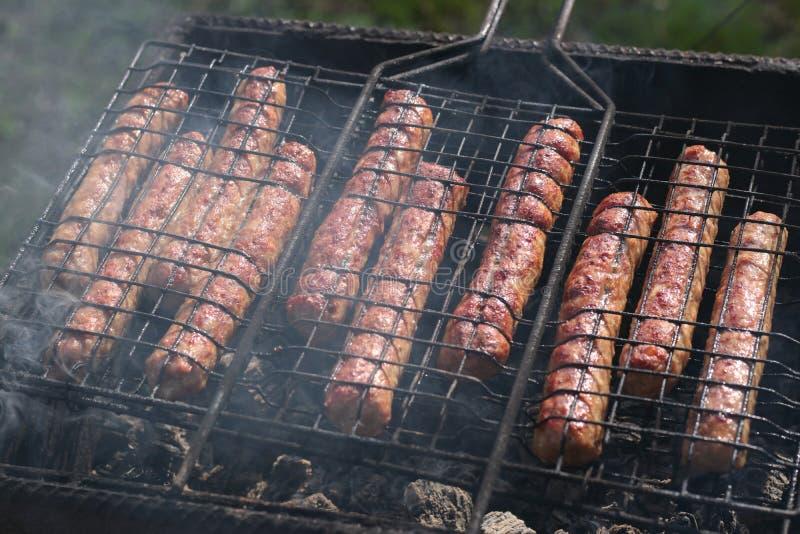 La carne suculenta frió las salchichas fritas en la parrilla en las ascuas imagen de archivo libre de regalías