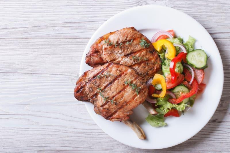 La carne suina ha grigliato con la vista superiore dell'insalata della verdura fresca immagine stock