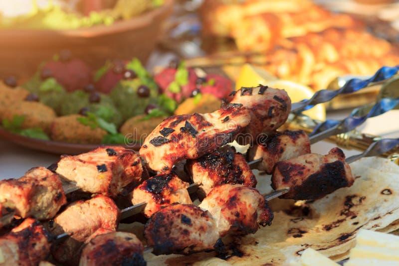 La carne suina piccante grigliata sullo shashlik tradizionale del fuoco con altri alimenti sull'evento ha servito la tavola immagine stock libera da diritti