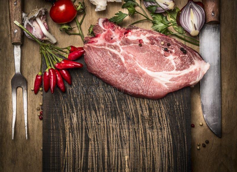 La carne suina taglia con le erbe e le spezie fresche per la cottura, la forcella ed il coltello su fondo di legno rustico, vista fotografia stock libera da diritti