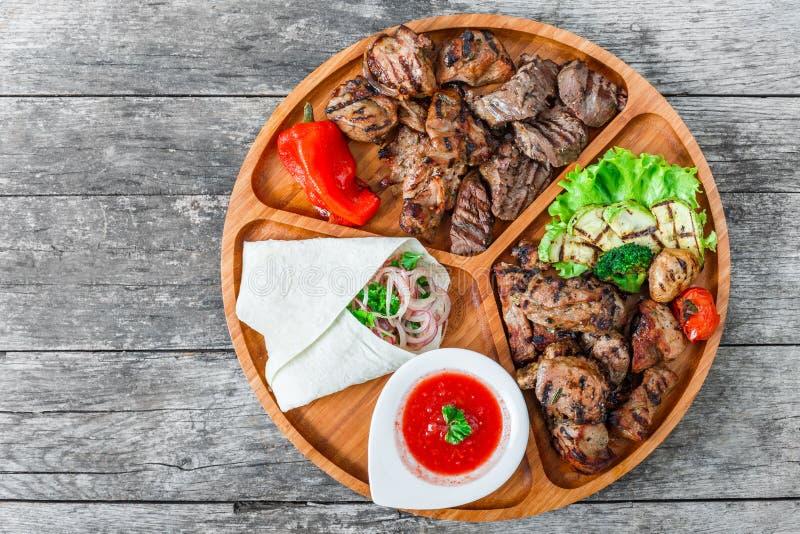 La carne y las verduras asadas a la parrilla deliciosas clasificadas con la ensalada y el Bbq frescos sauce en tabla de cortar en imagenes de archivo