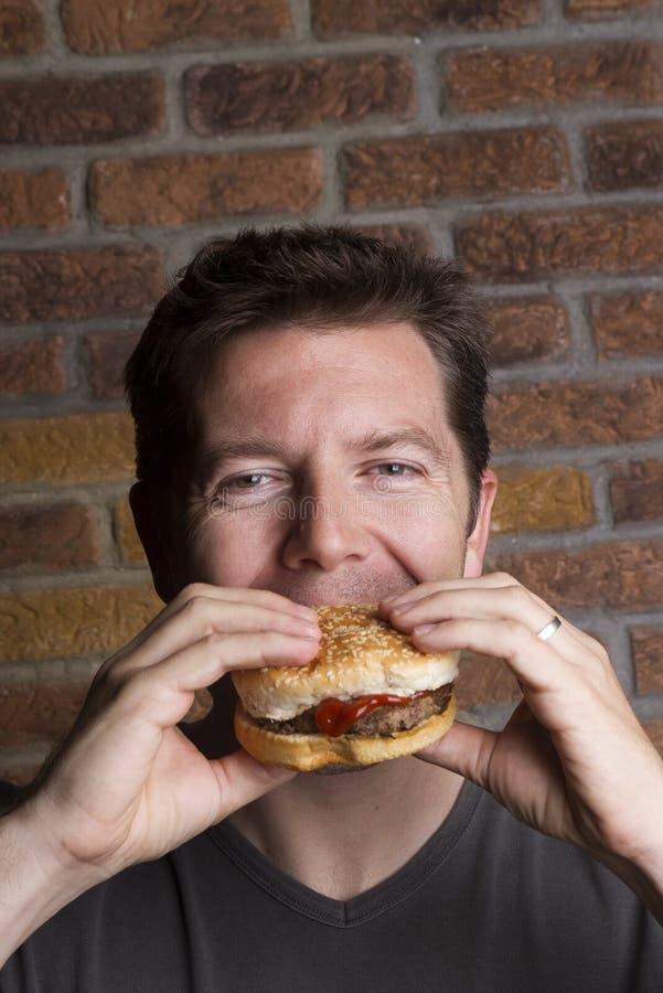 La carnivore mâle coule des dents dans l'hamburger photo libre de droits