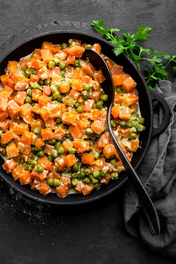 La carotte braisée avec les pois frais en sauce crémeuse à lait dans stewpan, légume font sauter sur le fond noir image stock