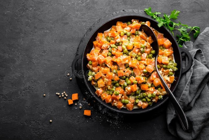 La carotte braisée avec les pois frais en sauce crémeuse à lait dans stewpan, légume font sauter sur le fond noir images libres de droits