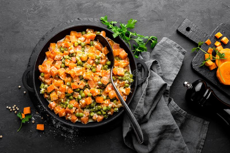 La carotte braisée avec les pois frais en sauce crémeuse à lait dans stewpan, légume font sauter sur le fond noir photo libre de droits