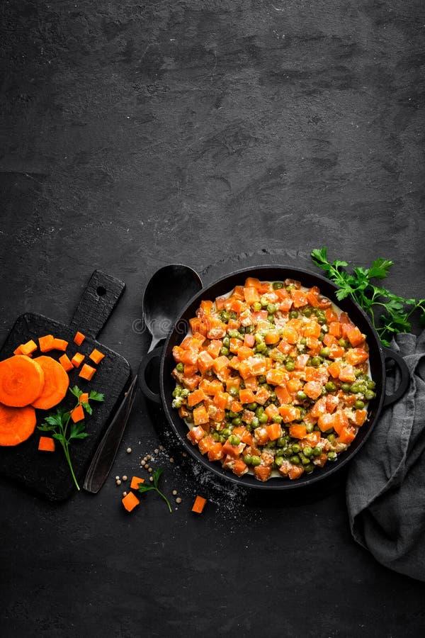 La carotte braisée avec les pois frais en sauce crémeuse à lait dans stewpan, légume font sauter sur le fond noir photographie stock libre de droits