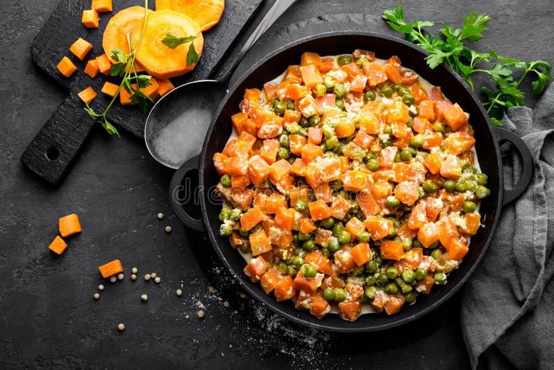 La carotte braisée avec les pois frais en sauce crémeuse à lait dans stewpan, légume font sauter sur le fond noir images stock