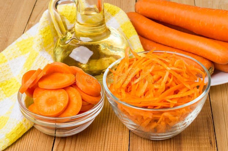 La carotte crue dans des cuvettes transparentes, mettent l'huile végétale et la serviette en bouteille image stock