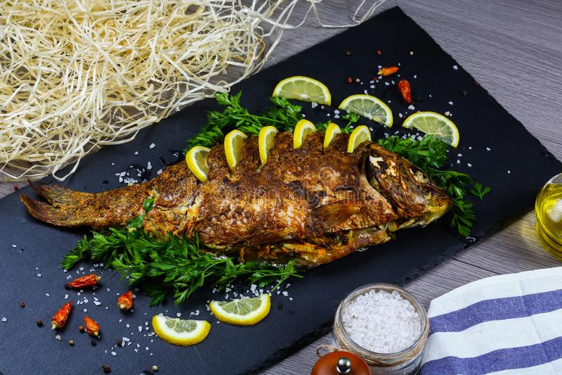 La carpe cuite au four délicieuse de poissons a bourré la croûte avec des légumes sur un panneau de schiste, faisant cuire la rec image libre de droits