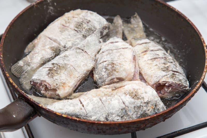 La carpe de poissons est faite frire dans une poêle photographie stock libre de droits