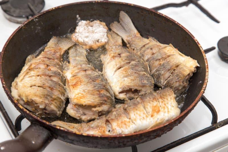 La carpe de poissons est faite frire dans une poêle photo stock