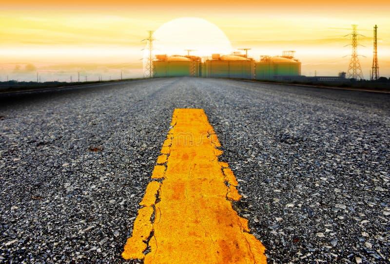 La carretera de asfalto a la fábrica industrial de los estados en el tiempo w de la tarde fotos de archivo libres de regalías