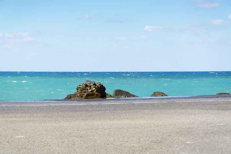La carretera de asfalto y la costa de mar alinean con el cielo azul en horizonte Paisaje en día de verano soleado imagenes de archivo